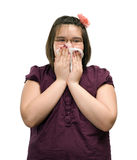 Coughing Child. A young girl holding a tissue to her mouth while she is coughing, isolated against a white background Royalty Free Stock Photos