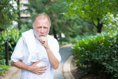 Coughing. Closeup portrait, old gentleman in white shirt with towel, coughing and holding stomach, isolated green trees and shrubs, outside outdoors background Royalty Free Stock Photography