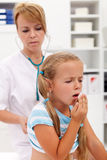 Coughing little girl on health checkup Stock Image