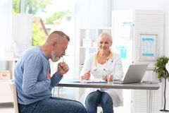Coughing mature man visiting doctor stock photography