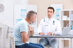 Coughing mature man visiting doctor stock photos