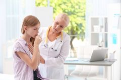 Coughing teenage girl visiting doctor. At clinic royalty free stock image