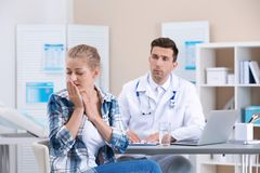 Coughing woman visiting doctor at clinic. Coughing young women visiting doctor at clinic Royalty Free Stock Images