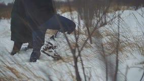 Coule de ornitólogos camina a través de nieve profunda y las nieves acumulada por la ventisca a un ` s del pájaro jerarquizan en  metrajes