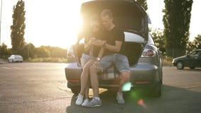 Coule feliz que se sienta en el tronco de coche abierto Muchacha bonita con callejones sin salida y gafas de sol que enrollan su  almacen de video