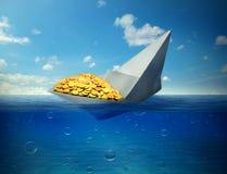 Couler le bateau transportant le symbole d'or des prix des produits de base en baisse Photos libres de droits