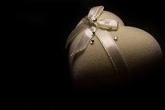 Couleur beige de belle boîte en forme de coeur molle avec l'arc sur le dessus sur le fond noir Images libres de droits