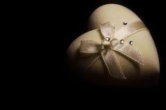 Couleur beige de belle boîte en forme de coeur molle avec l'arc sur le dessus sur le fond noir Image libre de droits