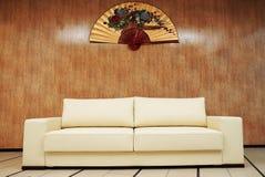 Couleur beige de sofa en cuir élégant sur un en bois Image libre de droits