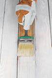 Couleur blanche de peinture de brosse de participation de main sur le bois Image stock