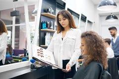 Couleur bouclée de cueillette de jeune fille pour des cheveux modifiant la tonalité se reposer dans le salon beaty photos stock