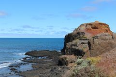 Couleur-contraste de pierre noire de lave et de sol rouge avec l'océan bleu et de ciel au cap Schank sur la péninsule de Morningt images libres de droits