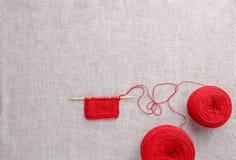 Couleur de fil de laine du rouge avec les aiguilles de tricotage en bois Images stock