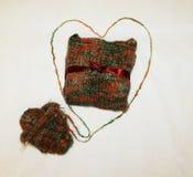 Couleur de photo, cadeau chaud et tricoté attaché avec un arc avec un écheveau de fil sur un fond blanc Images libres de droits