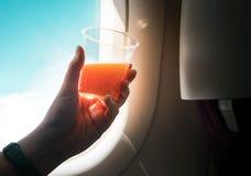 Couleur de vintage de femelle buvant du jus d'orange sur l'avion photographie stock