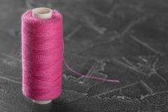 Couleur rose de fil de couture sur la bobine en plastique Objet sur un fond concret gris Photo stock