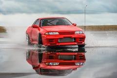 Couleur rouge de Nissan Skyline R 32 sur une route humide photo stock