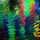 Couleurs allumant la réflexion dans l'eau images stock