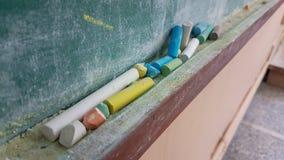 Couleurs de craies pour la classe d'école sale verte en bois de table Images stock