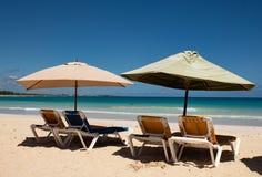 Couleurs des Cara?bes : lits pliants et parapluies sur la plage publique, la mer bleue intense et le ciel : paradis tropical photo stock