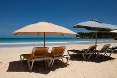 Couleurs des Cara?bes : lits pliants et parapluies sur la plage publique, la mer bleue intense et le ciel : paradis tropical photo libre de droits