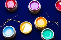 Couleurs lumineuses pour une manucure sur le fond bleu jaune renversé de peinture mouillé Image libre de droits