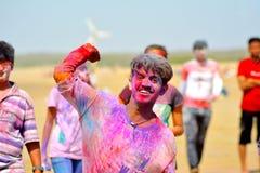 Couleurs throughing de garçon chez l'appareil-photo/Mandvi, Kutch, Inde - mars 2017 - couleurs throughing de garçon indien Image stock