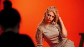 Coulisse: blonde het vrouwelijke model stellen voor fotograaf in rode studio stock videobeelden