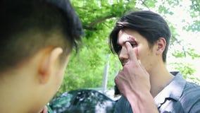 Coulisse van het toepassen van make-up voor zombieapocalyps het schieten Een gebroken wenkbrauw stock footage