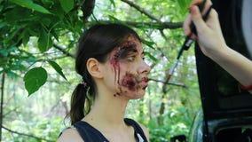 Coulisse van het toepassen van make-up voor zombieapocalyps het schieten Zombiemake-up op een jonge vrouw stock footage