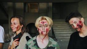Coulisse van zombieapocalyps het schieten Actoren die in de rij en het stellen staiding Portret dat van de make-up wordt geschote stock footage