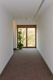 Couloir avec la fenêtre en bois à l'extrémité Photo stock