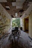 Couloir désolé et détérioré avec le fauteuil roulant - hôpital abandonné Photos stock