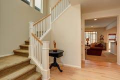 Couloir lumineux dans des tons crémeux avec le plancher en bois dur et l'escalier image libre de droits