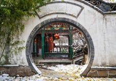 Couloir traditionnel historique derrière une porte de lune de Pékin, Chine en hiver avec la neige photographie stock libre de droits