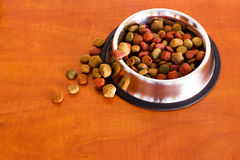 Coulourfull Dog Food Grains. Brown red green and orange dog food grains in a dog dish laying on the floor Royalty Free Stock Photography