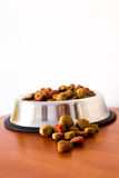 Coulourfull Dog Food Grains. Brown red green and orange dog food grains in a dog dish laying on the floor Stock Photos
