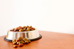 Coulourfull Dog Food Grains. Brown red green and orange dog food grains in a dog dish laying on the floor Stock Image