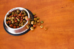 Coulourfull Dog Food Grains. Brown red green and orange dog food grains in a dog dish laying on the floor Stock Photo