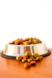 Coulourfull Dog Food Grains. In a silver dog dish lying on the floor red brown yellow and green grains Royalty Free Stock Image