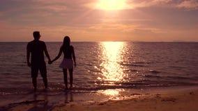 Coulpe romántico que camina en la playa en la puesta del sol almacen de metraje de vídeo