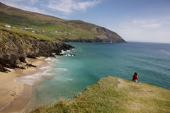 Coumeenoole beach. Woman sitting on a rock and looking at Coumeenoole beach strand, Dingle peninsula, co Kerry, Ireland Royalty Free Stock Photography