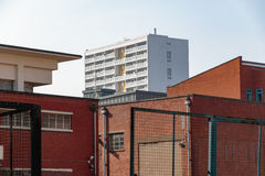 Council housing high rise flats in East London. Surrounded by red brick industrial looking buildings Stock Photo