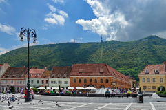 Landmark attraction in Brasov, Romania. Panorama of the Council Square. Tampa Mountain in the background Royalty Free Stock Images