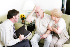 Counseling - Feeling Guilty. Senior couple in therapy. Husband is feeling guilty stock photo