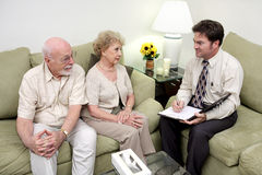Counseling or Sales Call Overview. A marriage counselor or salesman meeting with a senior couple.  The wife is receptive but the husband looks skeptical Stock Images