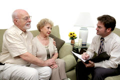 Counseling Session or Salesman. A senior couple speaking with a marriage counselor.  Could also be a salesman in their home.  Isolated on white with focus on Stock Photo