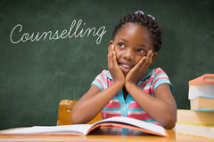 Counselling against green chalkboard. The word counselling and pupil sitting at her desk  against green chalkboard Stock Image
