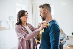 Counsellor putting an adhesive notes on client during group therapy. A counsellor putting an adhesive note with negative emotions words on client during group stock photo