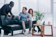 Counselor with clipboard talking to upset couple sitting. On couch stock images